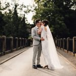 Real Bride Rachel wears Violet by Eliza Jane Howell - Kissing on the bridge