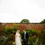 Real Bride Ruth in Loretta by Naomi Neoh - Bride & Groom by wall