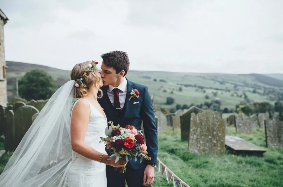 Real Bride Lucy wears Charlie Brear 1920.2 - Bride & Groom Kissing Church Yard- Cicily Bridal Leicestershire